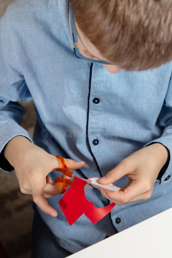 Boy in a blue shirt and glasses sits at a desk and concentrates on doing plastic work with colored paper. The boy is painting. Children`s hands hold a brown felt royalty free stock image