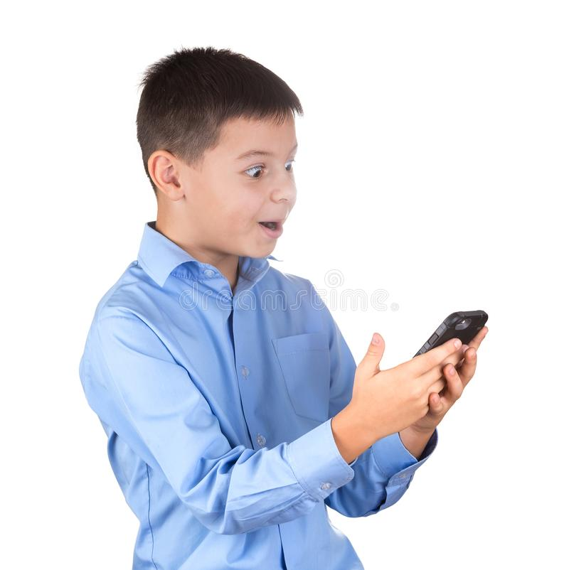 Boy in blue shirt looks at the phone screen with astonishment an royalty free stock image