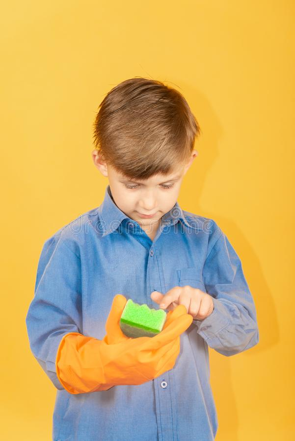 A boy in a blue shirt and orange gloves examines a green washing sponge royalty free stock images