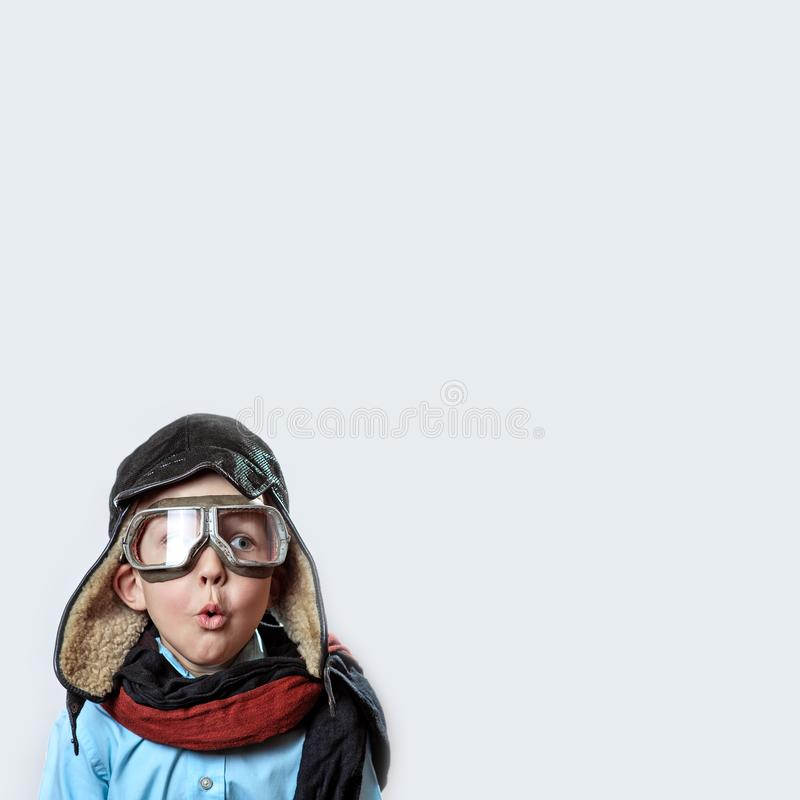 Boy in a blue shirt, pilot`s glasses, hat and scarf on a light background. A boy in a blue shirt, pilot`s glasses, hat and scarf on a light background royalty free stock photography