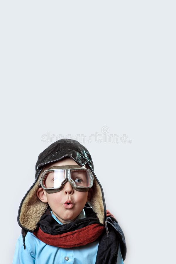 Boy in a blue shirt, pilot`s glasses, hat and scarf on a light background. A boy in a blue shirt, pilot`s glasses, hat and scarf on a light background royalty free stock photos