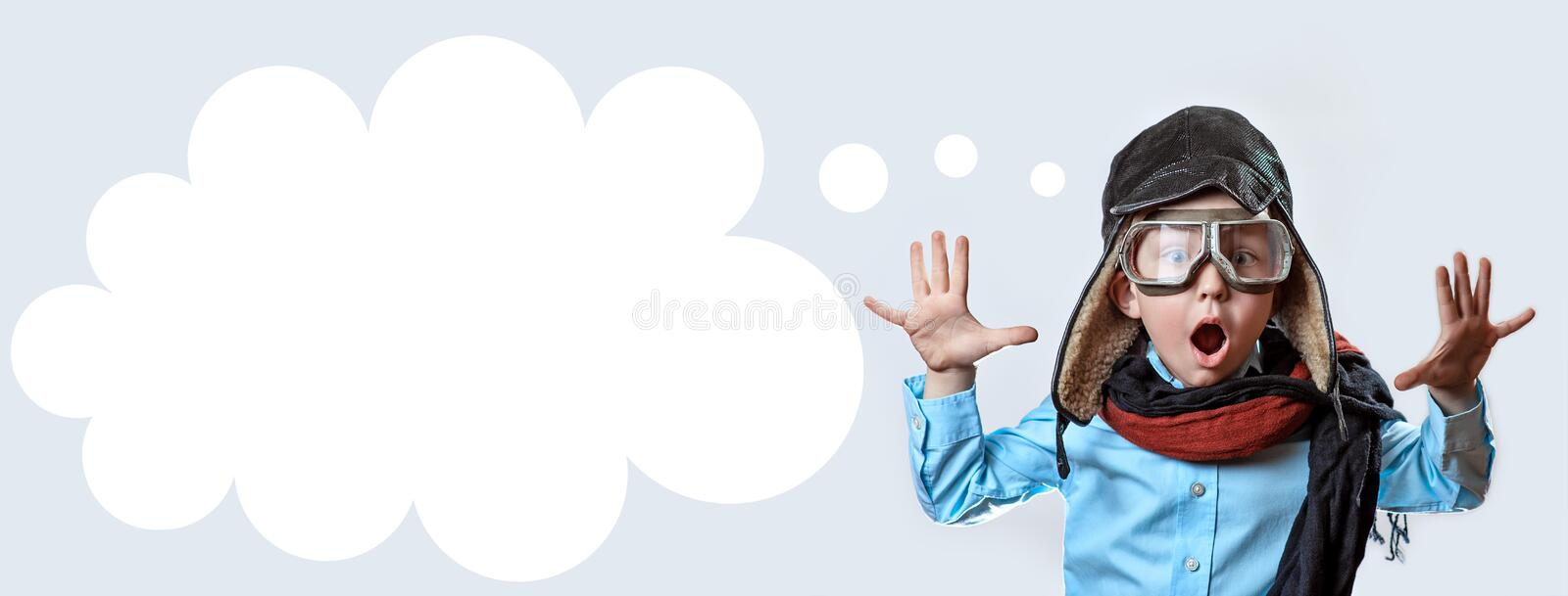 Boy in a blue shirt, pilot`s glasses, hat and scarf raised his hands on a light background stock photos