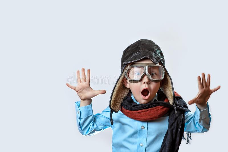 Boy in a blue shirt, pilot`s glasses, hat and scarf raised his hands on a light background. A boy in a blue shirt, pilot`s glasses, hat and scarf raised his royalty free stock photos