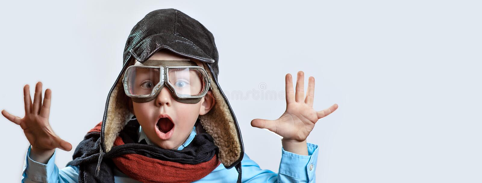 Boy in a blue shirt, pilot`s glasses, hat and scarf raised his hands on a light background. A boy in a blue shirt, pilot`s glasses, hat and scarf raised his royalty free stock photo