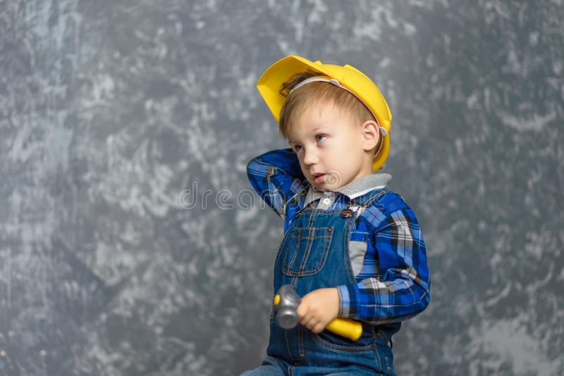 A boy in a yellow construction helmet, scratches his head and holding a hammer stock photography