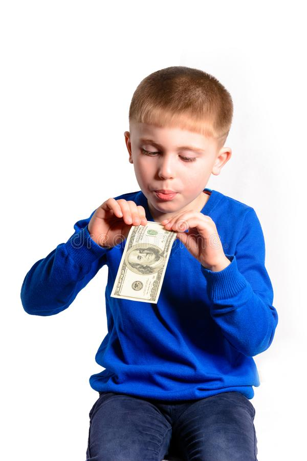 A boy in a blue sweater blowing on a bill, isolated on a white background royalty free stock photo