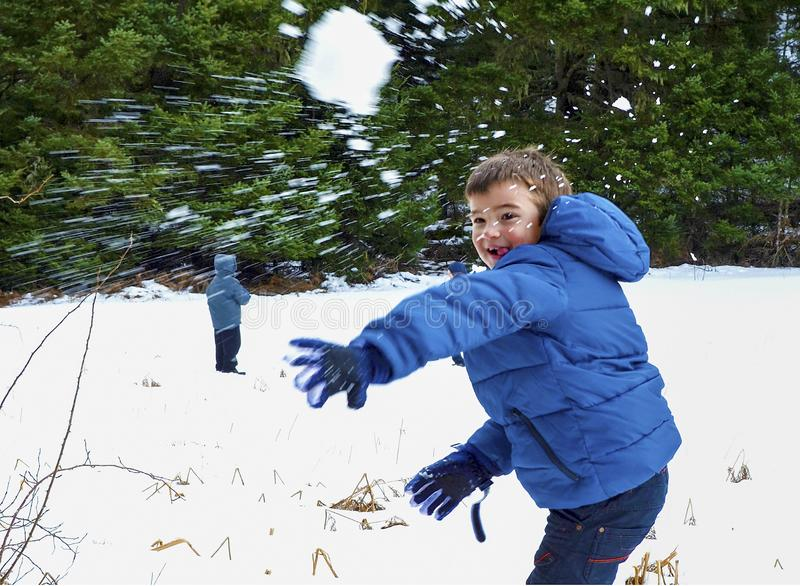 Boy in blue warm coat having fun in beautiful winter place with snowballs. royalty free stock photography