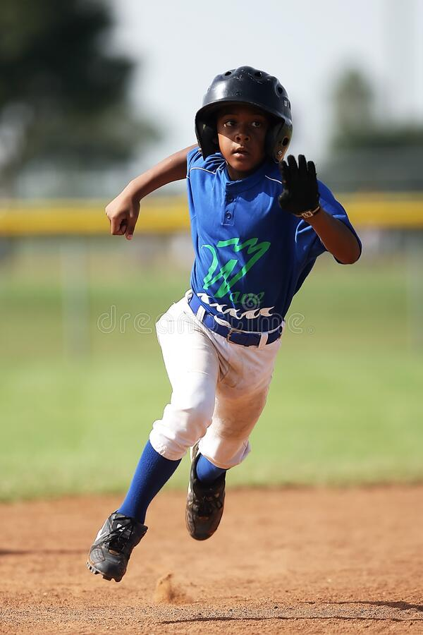 Boy in Blue and White Baseball Jersey Running on Brown Soil Field during Daytime stock photography