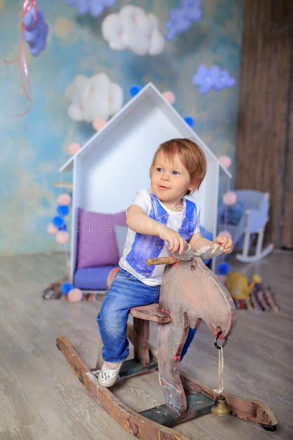 Boy in Blue and White Crew Neck T Shirt Riding on Wooden Rocking Moose stock image