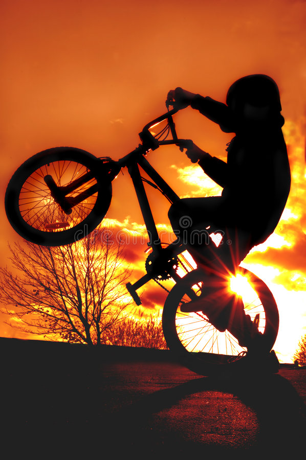Boy on BMX silhouette stock photography