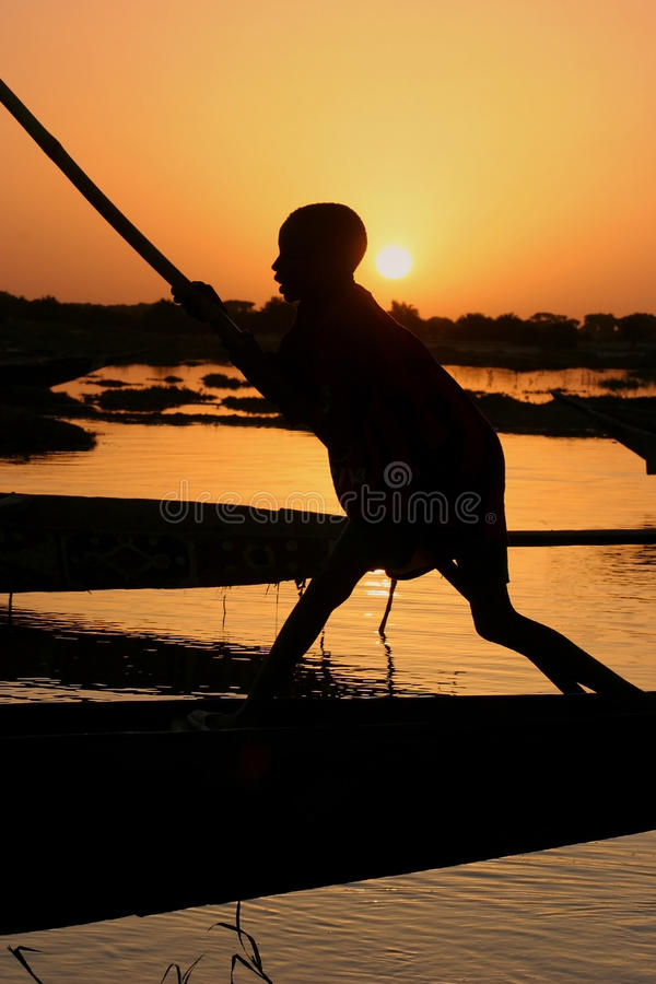 Download Boy On A Boat On The Niger River Stock Photo - Image of orange, sunset: 17652564