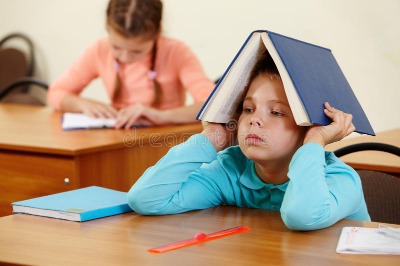 Boy with book. Cute schoolboy keeping open book on head in classroom royalty free stock photo