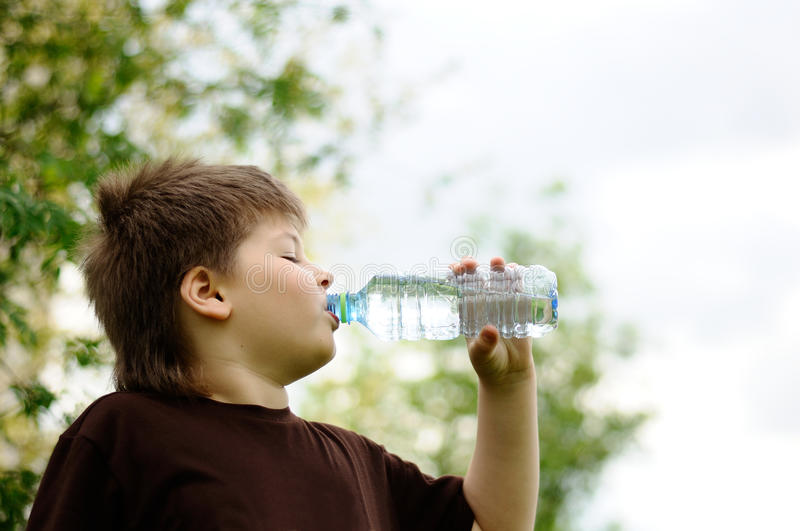 Boy with a bottle of water in nature stock photography