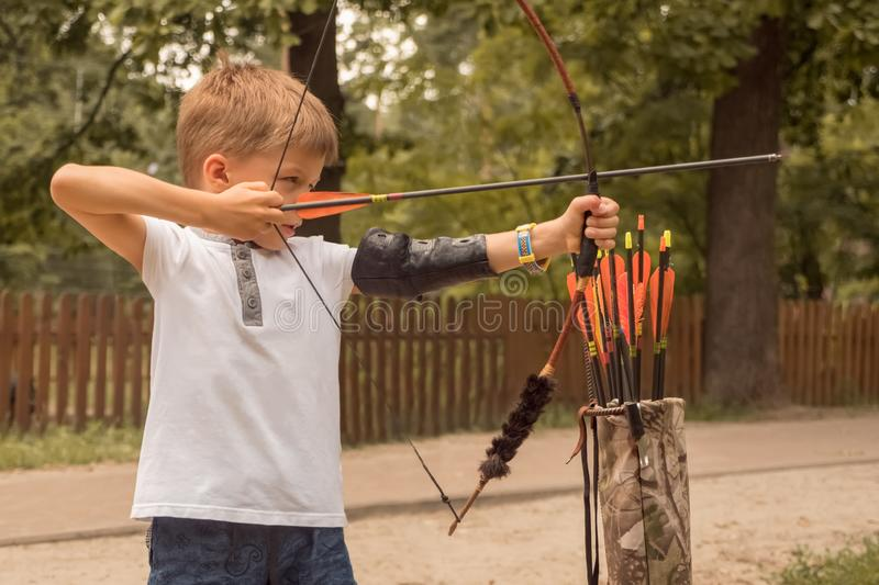 Boy with a bow and arrow. Children and sports. Archery background. Junior Archery school. Boy with bow and arrow concentrated on target. Kid stared at target stock photo