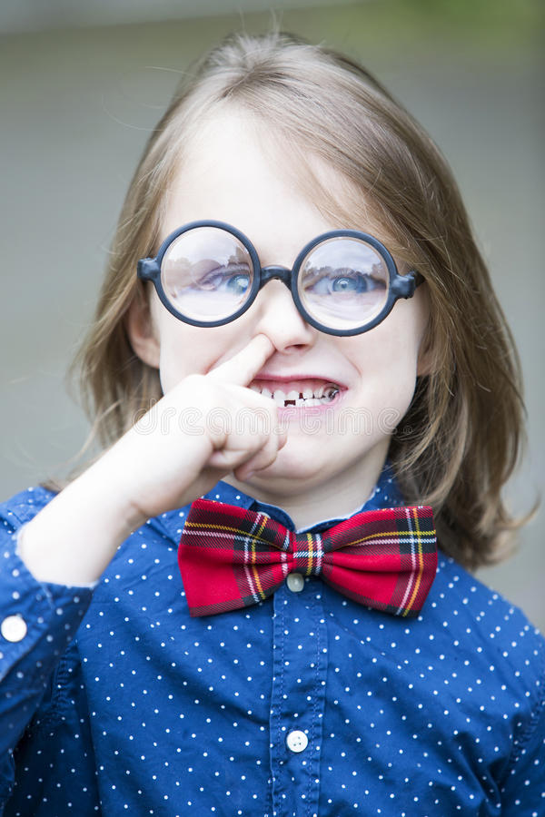 Boy with bow tie and big glasses picking his nose royalty free stock images