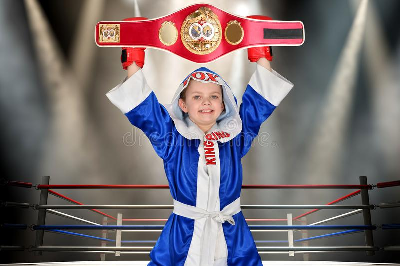 Boy boxer holding championship belt in Boxing. Little champion.The big wins. stock photography