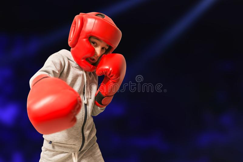 The boy in boxing gloves  ready to fight. Young Boxer fighter over black background. Power concept of strength training.  stock photography