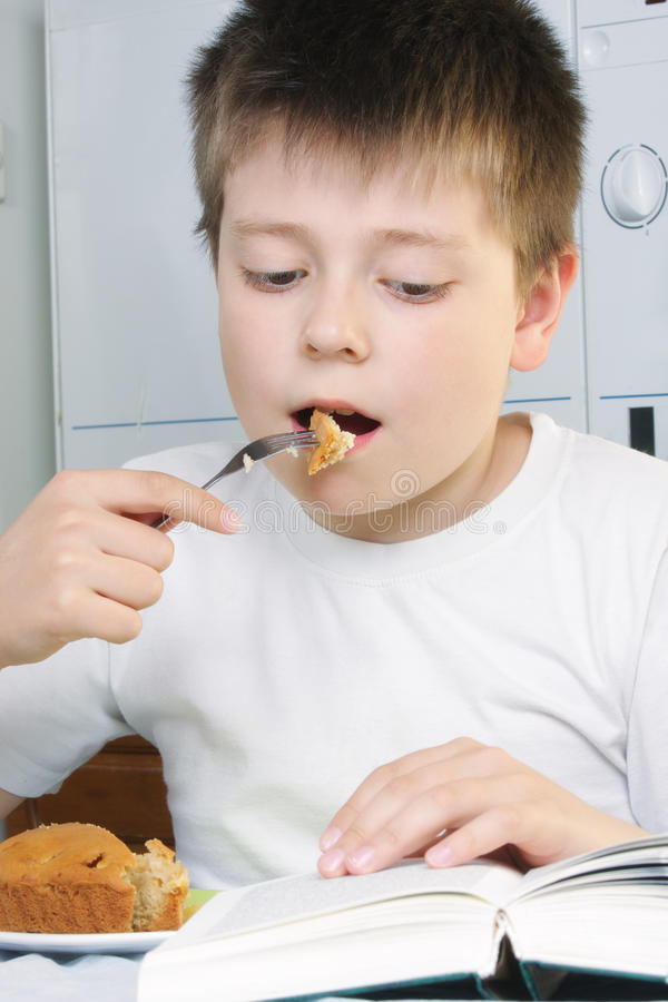 Boy at breakfast with book stock image