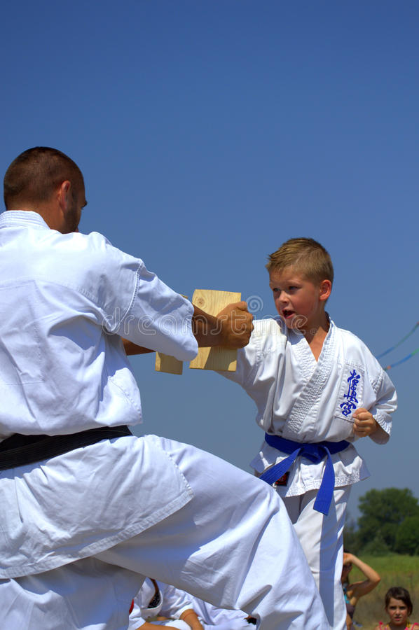 Boy breaking board in martial arts practice. Young boy member of Karate Kyokushin martial art club breaking the wooden board in half at outdoor show stock photos