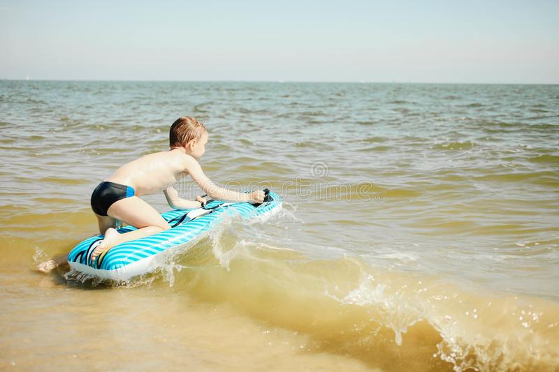 Boy with bright blue inflatable mattress swims in sea stock image