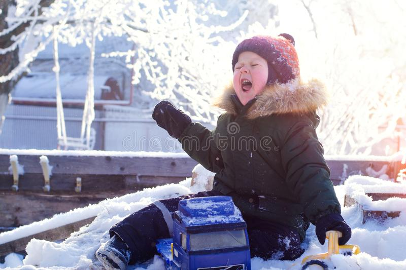 A boy in a bright orange hat plays with toys in a snowy winter Park royalty free stock images