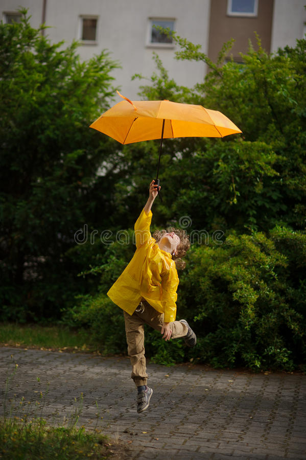 Boy in bright yellow raincoat flies over the earth with an umbrella in a hand. The boy in a bright yellow raincoat flies over the earth with an umbrella in a stock image