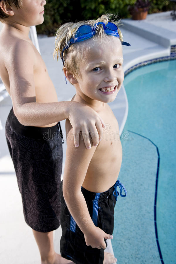 Boy with brother grinning at side of swimming pool stock image