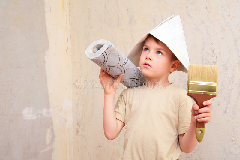 Boy with brush and roll of wallpaper in papper hat. Little boy with brush and roll of wallpaper in papper hat stock images
