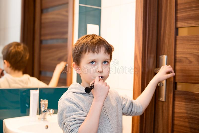 Boy brushing his teeth in the bathroom royalty free stock photography