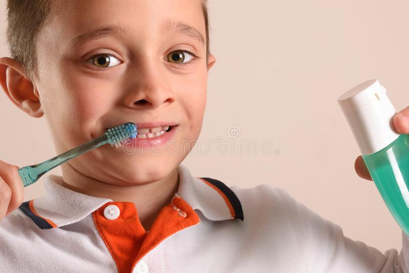 Boy brushing teeth with toothbrush on isolated brown stock photo