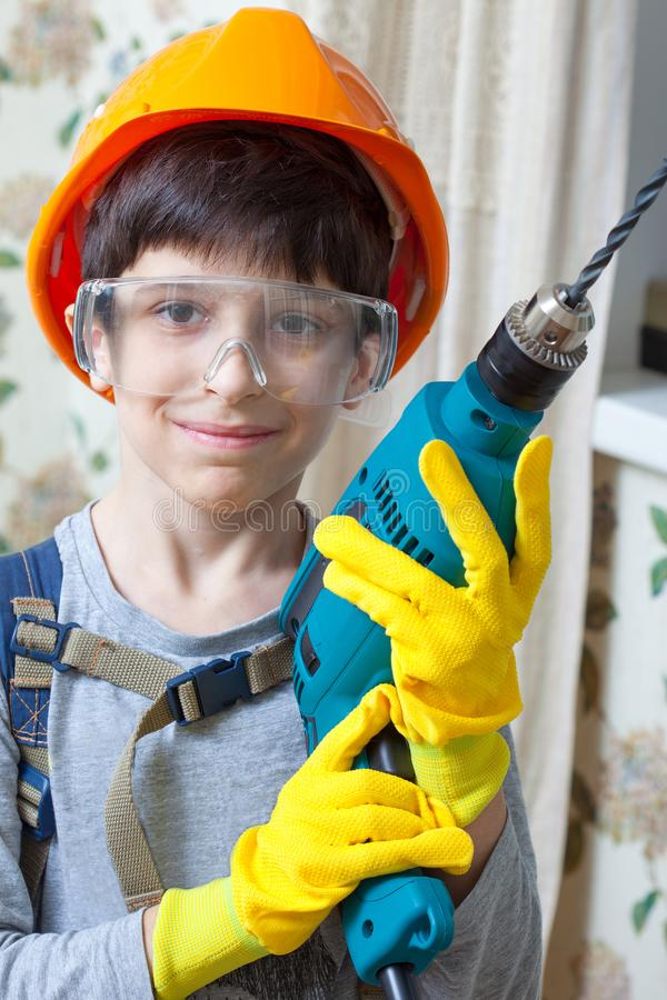 Boy builder in goggles and with a drill stock image