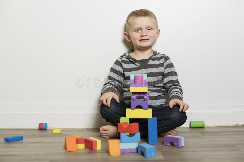 Boy building with blocks sit on the floor royalty free stock images