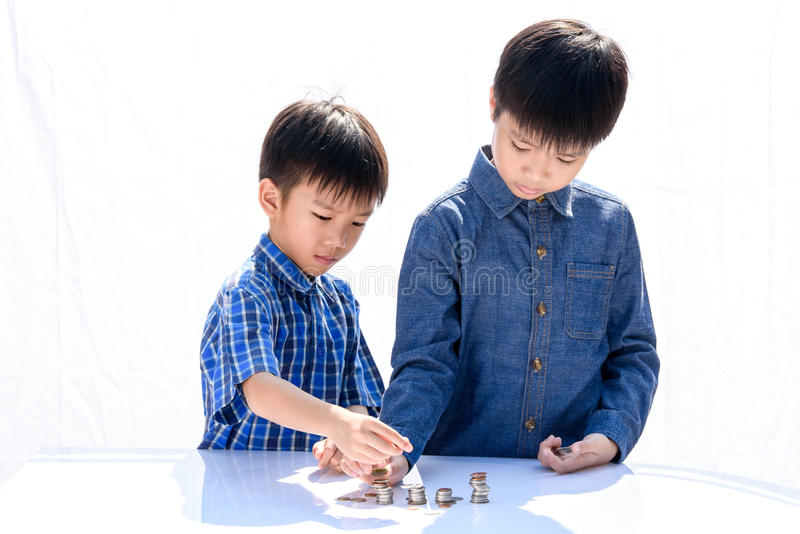 Boy building coin tower. Young happy Thai boy build a tower by a coin on white background royalty free stock image