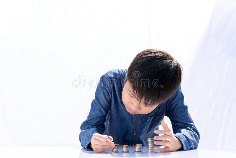 Boy building coin tower stock photo