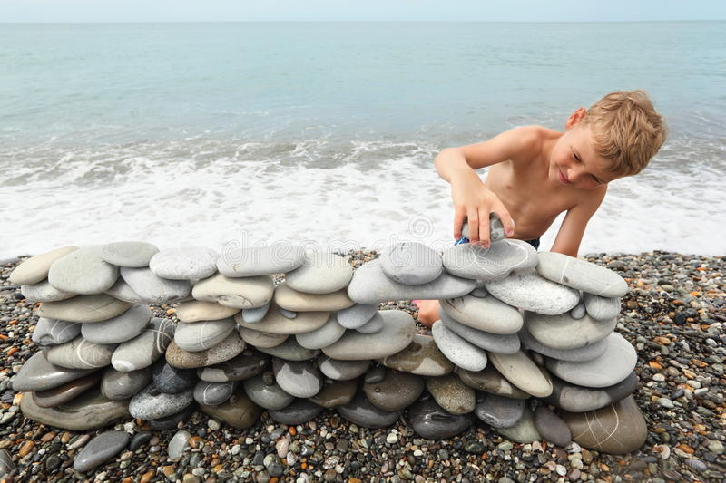 Boy is building construction of pebbles on sea royalty free stock photos