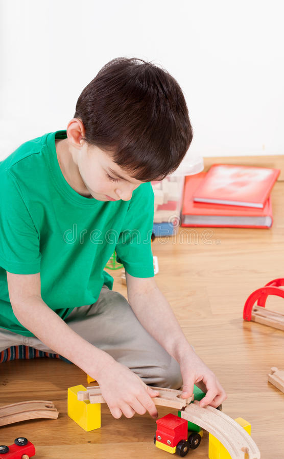 Boy building racetrack. Vertical view of a boy building racetrack royalty free stock photography
