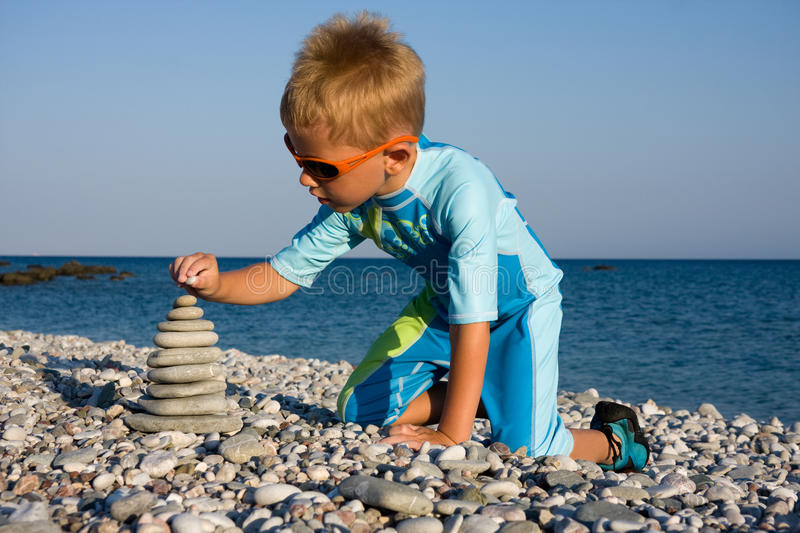 Boy building stone stack on beach royalty free stock photo