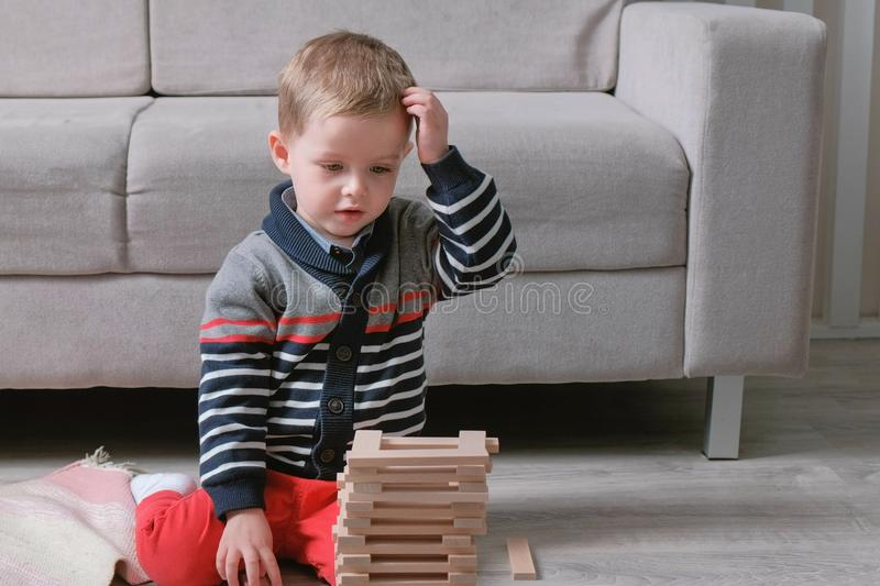 Boy is building a tower from wooden blocks sitting on the floor by the sofa. stock images