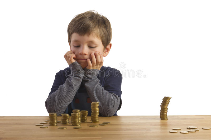 Boy building towers out of money royalty free stock image