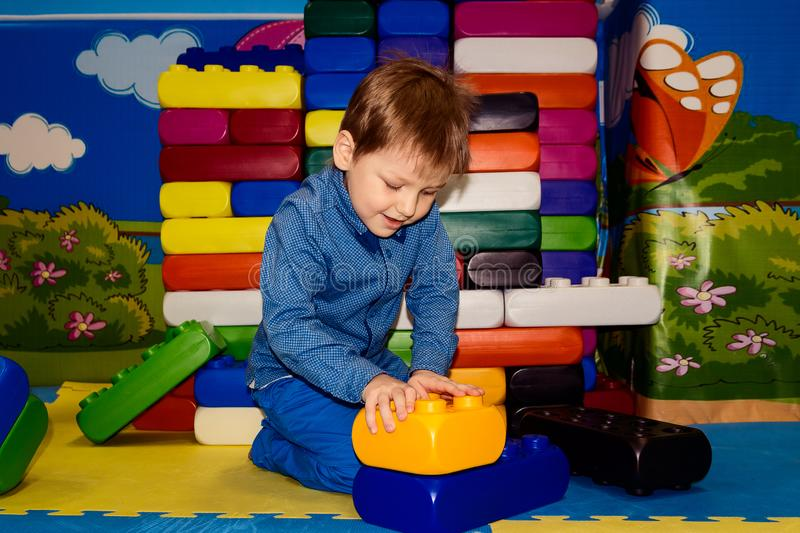 Boy builds a pyramid of large parts of the designer stock photo