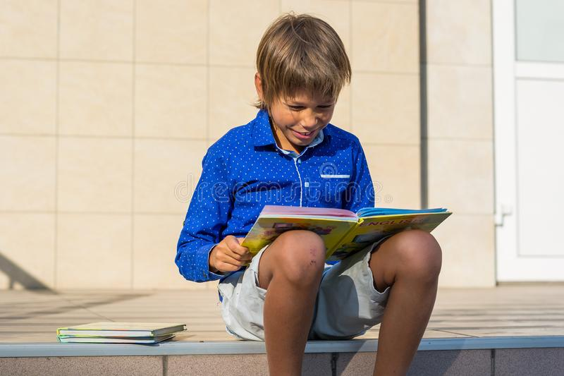 Boy-bully sits on the steps in front of the school and reads the stock images