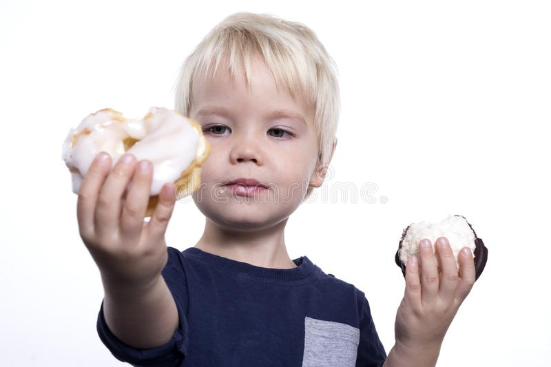 Boy with cakes. Kid eating cakes on a white background, children obesity royalty free stock photography