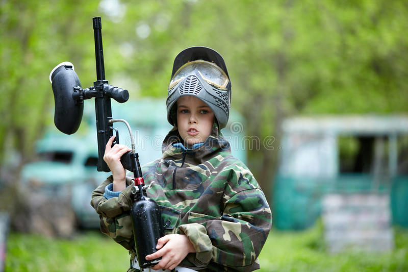 Boy in camouflage holds a paintball gun barrel up stock photos