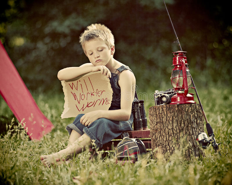 Boy camping in countryside. Young boy camping in in countryside next to tent with sign and fishing rod stock image