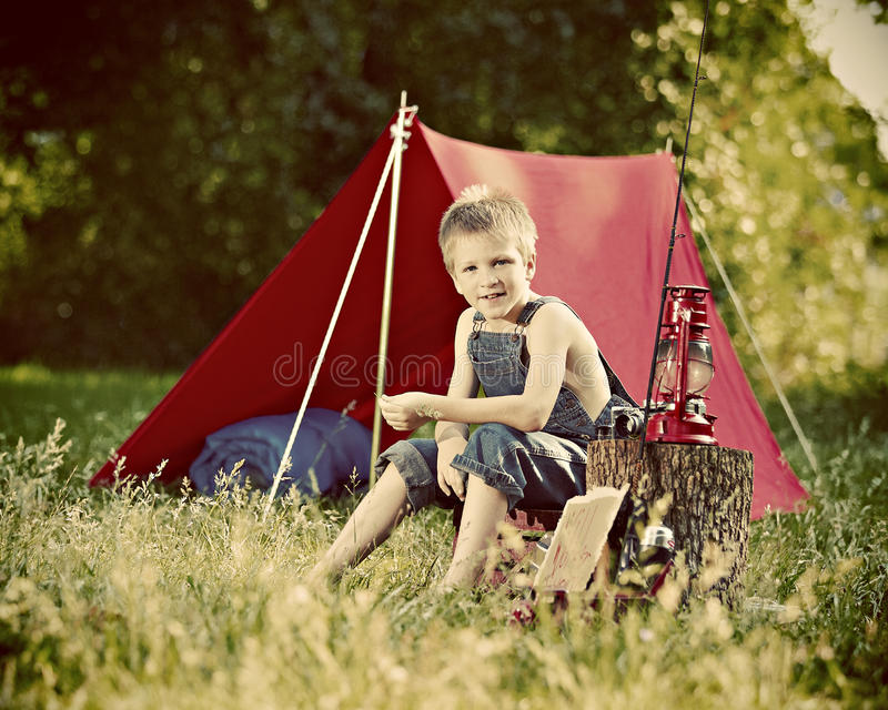 Boy camping with tent. Young boy camping in countryside with tent, fishing rod and lantern royalty free stock images