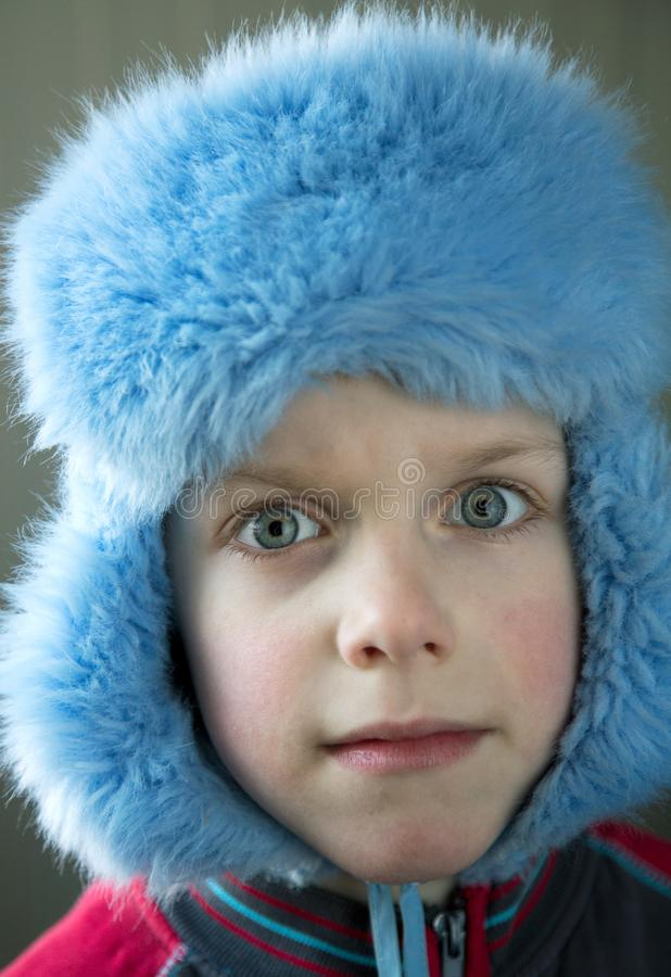Boy in a cap with earflaps with bulging eyes. Close up royalty free stock image