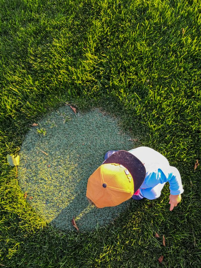 Happy kid wearing brown cap hat sitting in the park green grass with bright light sunny day royalty free stock photography
