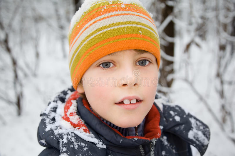 Boy in cap with snow on shoulders in winter royalty free stock photography