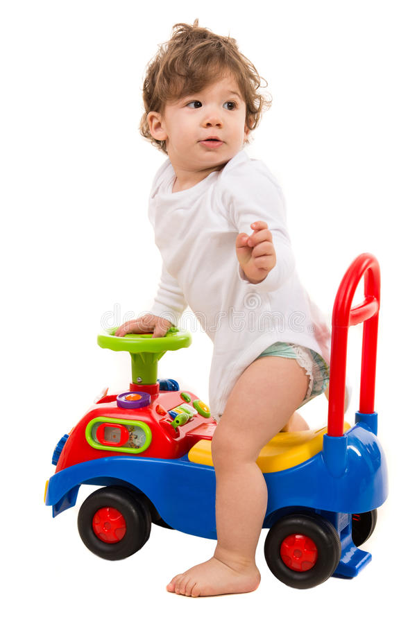 Boy in a car toy looking back stock photo
