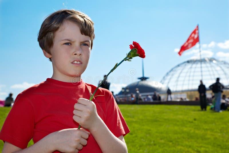 Boy with carnation stands on Poklonnaya Hill. Boy in the red t-shirt with red carnation in the hands stands on Poklonnaya Hill on Victory Day royalty free stock photography